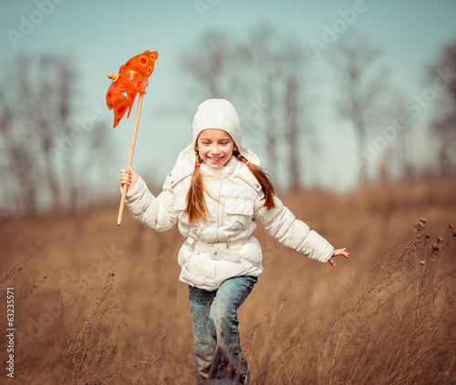 little girl holds windmill in hand