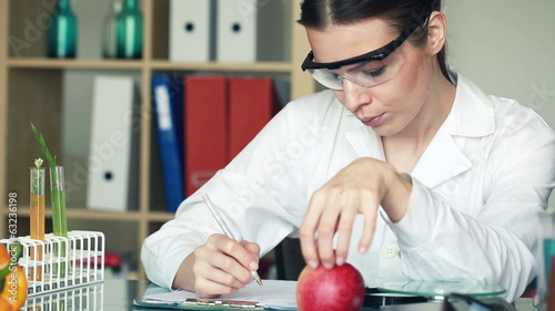 Female biochemist examine apple and writing results in lab