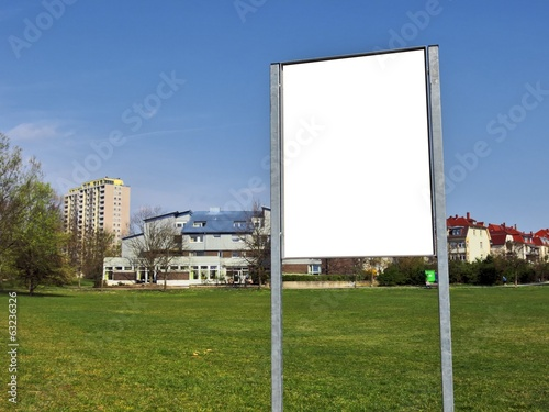 Empty billboard on green field