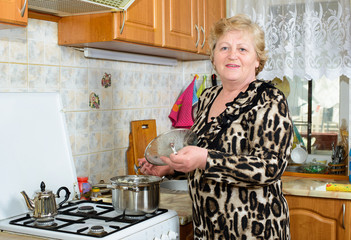 Senior woman cooking at the kitchen