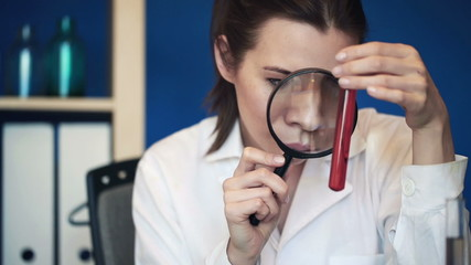 Chemist examine test tubes with chemicals through magnifying gla