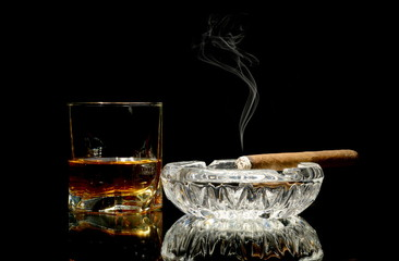 Whisky and a cigar on glossy table