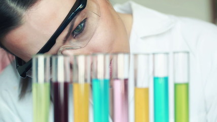 Female chemist looking at test tubes with chemicals in laborator