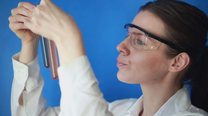 Female chemist comparing, looking at test tubes with chemicals