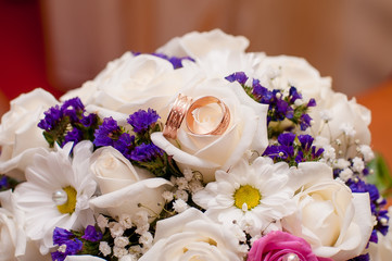 Wedding bouquet of beautiful roses and and rings