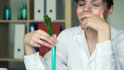 Unhappy biochemist looking at dead plant in test tube