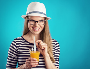Happy smiling blonde in white hat holding glass of cocktail