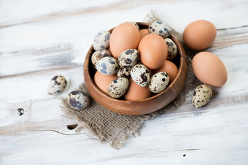Raw quail and brown chicken eggs, high angle view, studio shot