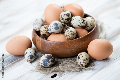 Wooden bowl with raw quail and brown chicken eggs, close-up