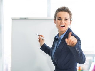 Business woman near flipchart pointing on listener