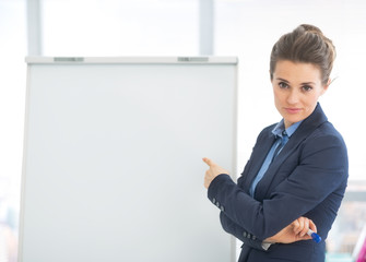 Business woman pointing on flipchart