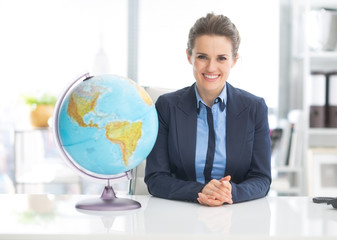 Portrait of happy business woman near earth globe