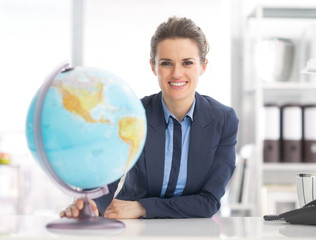 Portrait of happy business woman holding earth globe