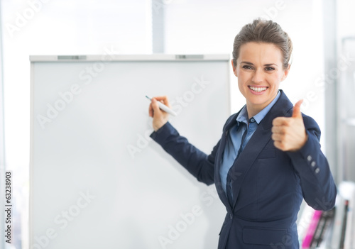 Smiling business woman near flipchart showing thumbs up