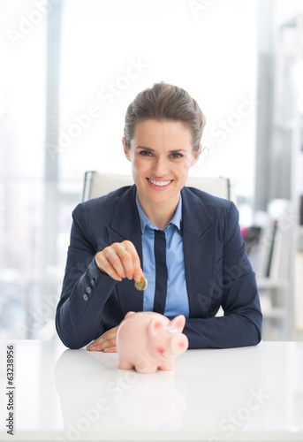Smiling business woman putting coin into piggy bank