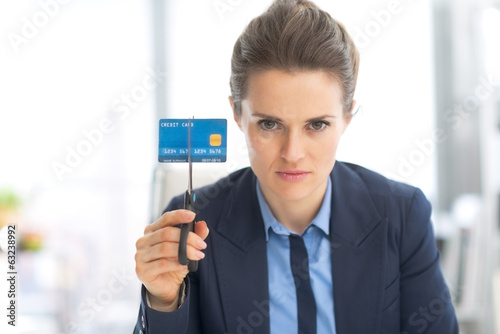 Serious business woman cutting credit card with scissors