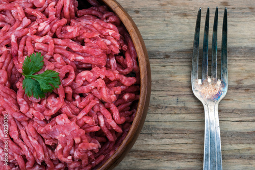 bowl of raw mince meat and fork on a wooden background