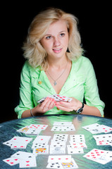 Woman displays playing cards on a table
