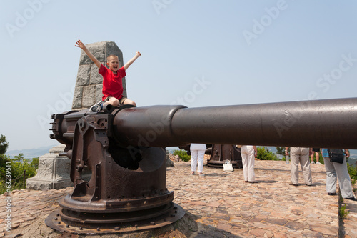 Boy on a gun in the old Russian fort