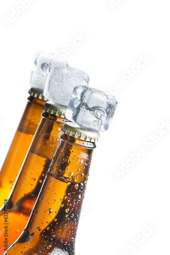 three tilted bottle of fresh beer with ice on top