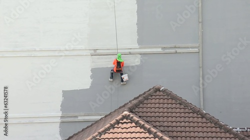 A man is hanging himself, painting the buiding. Security needed