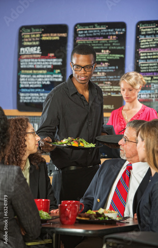 Man Serving Customers in Cafe
