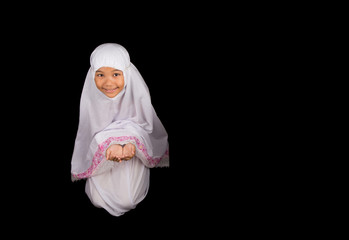 Young Asian Muslim girl in white hijab saying a prayer