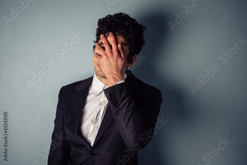 Stressed young businessman with headache