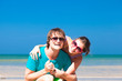 Portrait of happy young couple in sunglasses having fun on