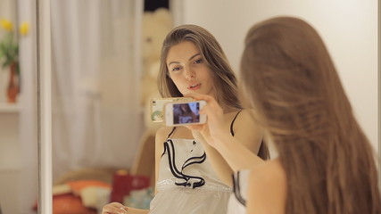 Young girl dances and takes a photo of herself before the mirror