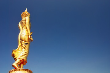 Standing Buddha with blue sky
