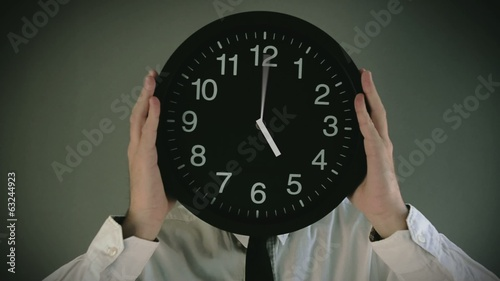 Wasting time. Businessman with clock in front of his head.