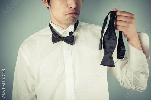 Young man holding a bow tie
