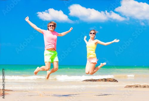 front view of young couple in bright clothes jumping on the