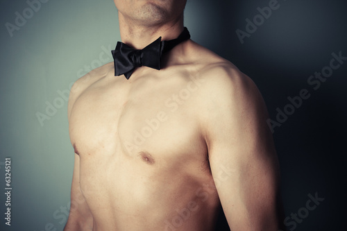 Young shirtless man with bow tie