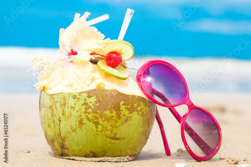 picture of fresh cocnut cocktail and red sunglasses on tropical