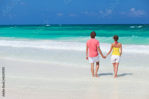 back view happy young couple in bright clothes walking to the