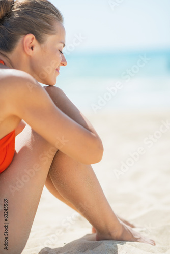 Relaxed young woman sitting on beach