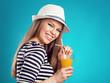 Active fresh summer girl drinking orange juice over blue