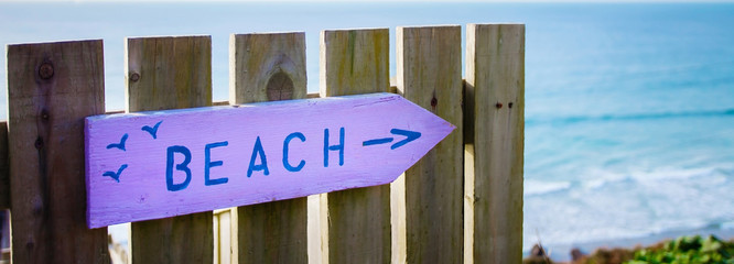Pink & blue beach sign path marker, in Summer, panorama.