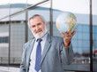 Senior businessman holding globe