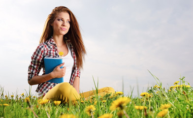 Young beautiful woman on green field and reads book.