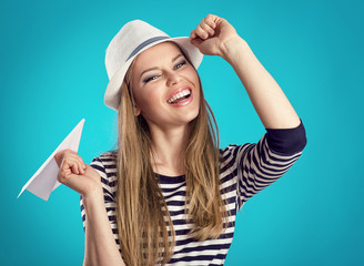 Happy woman in white hat with paper plane ready for trip