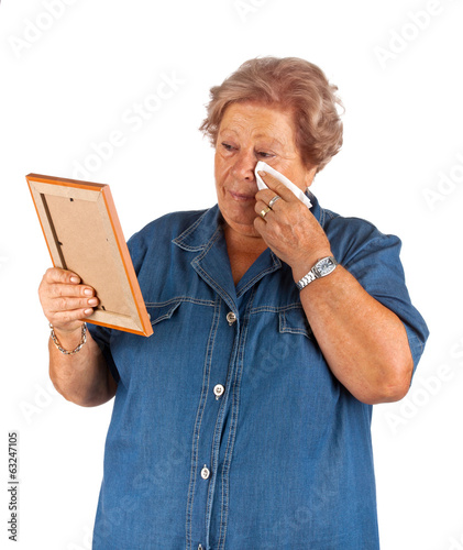 Old lady crying watching a blank photo frame