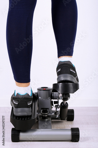 Woman doing exercise on stepper. Close-up on legs.