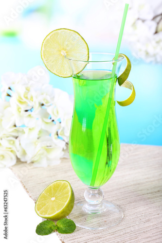 Glass of cocktail on table on light blue background
