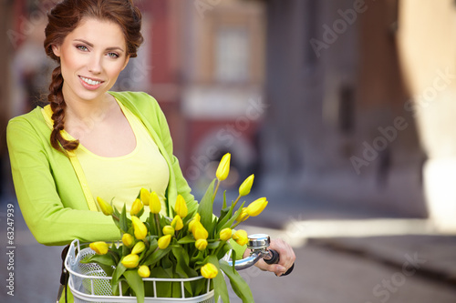Woman wearing a spring skirt like vintage pin-up holding bicycle