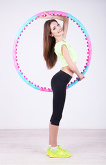 Woman doing exercises with hula hoop in room