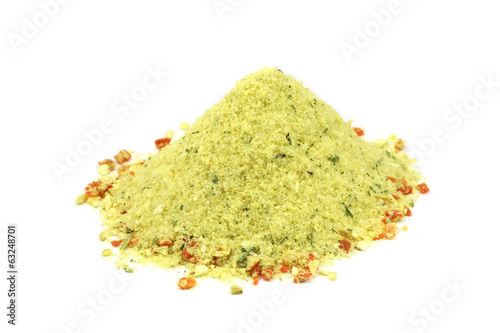 handful of yellow salt with spices on a white background