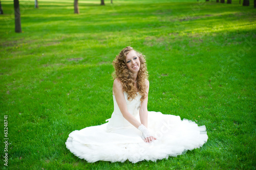 Beautiful bride in a white dress on green grass